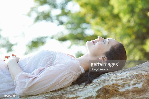 Profile of woman laying o tree trunk.