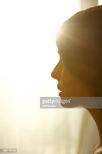 profile of woman looking towards the light - brightly lit stock pictures, royalty-free photos & images