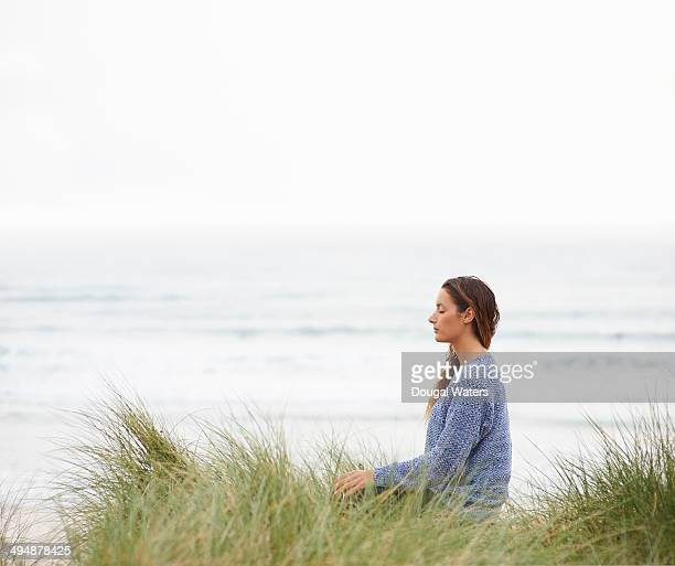 Profile of woman meditating at beach.