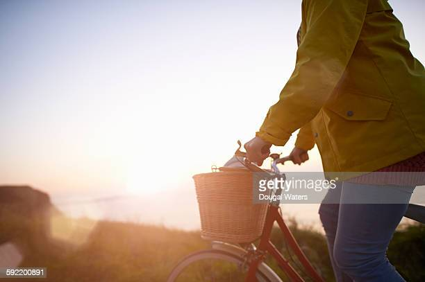 Profile of woman riding bicycle by sea.
