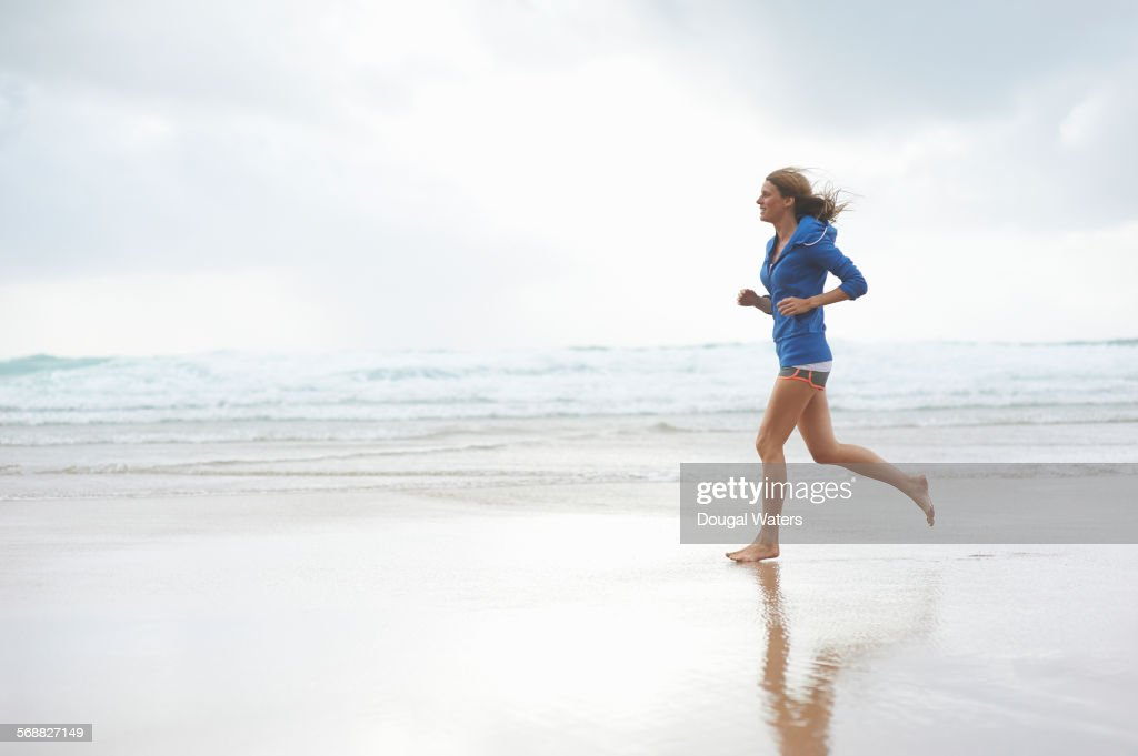 Profile of woman running at beach. : Stock Photo