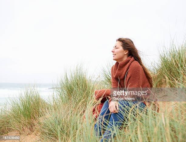 Profile of woman sitting amongst grasses at beach.