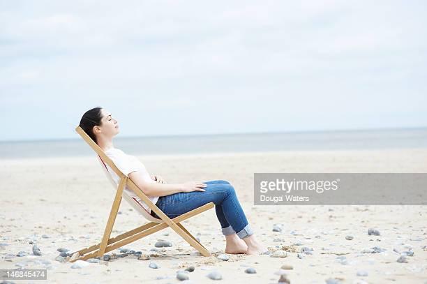 profile of woman sitting on deck chair at beach. - アウトドアチェア ストックフォトと画像