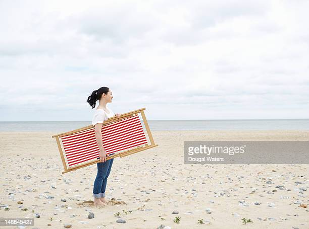 profile of woman standing at beach with deck chair - dougal waters stock pictures, royalty-free photos & images