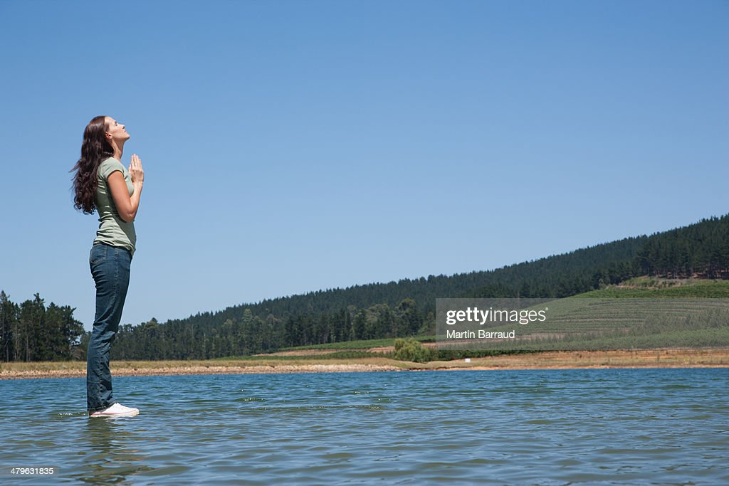 Profile of woman standing on water praying : Stock Photo