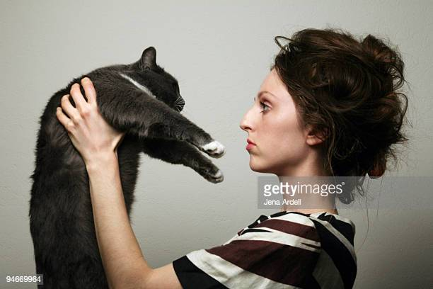 Profile of woman w/ messy hair holding gray cat