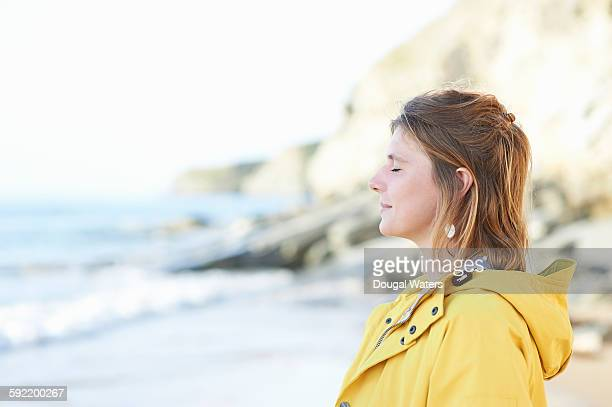 Profile of woman with eyes closed at beach.