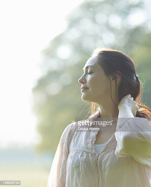 profile of woman with eyes closed in countryside. - mid adult women stock pictures, royalty-free photos & images