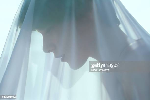 Profile of woman with green hair under blue veil
