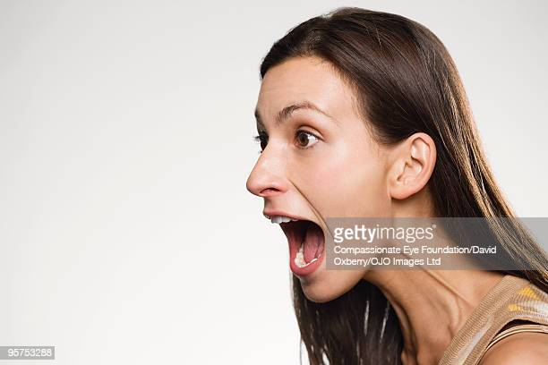 profile of woman yelling - mouth open stock pictures, royalty-free photos & images