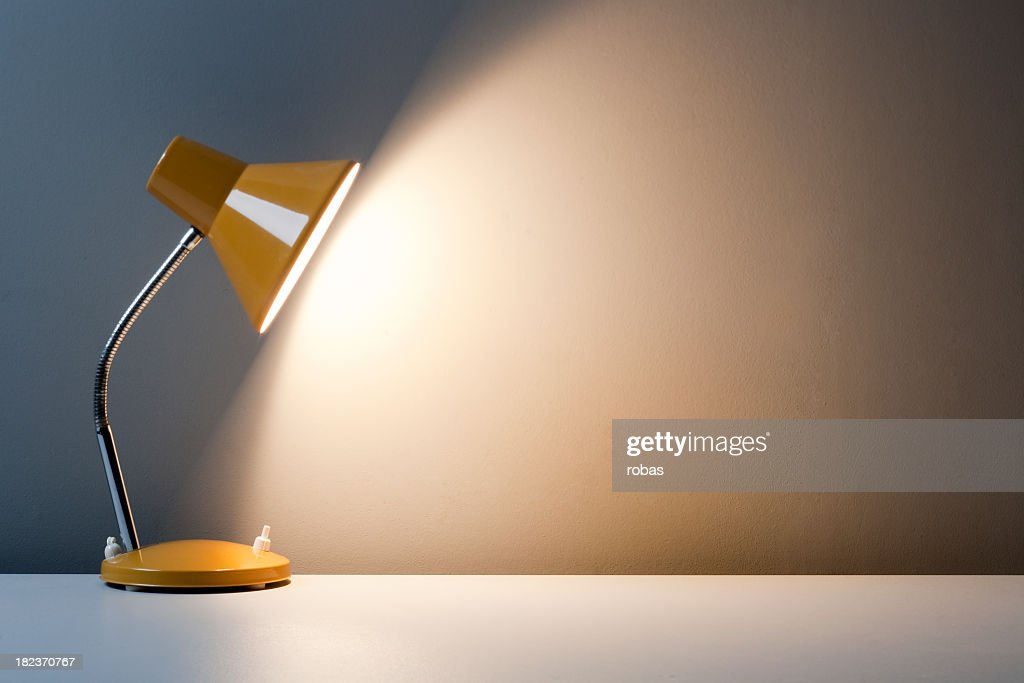 Profile of yellow desk lamp, turned on on white table : Stock Photo