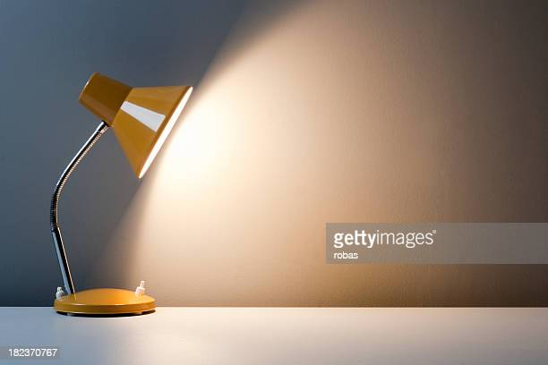 profile of yellow desk lamp, turned on on white table - electric lamp stock photos and pictures