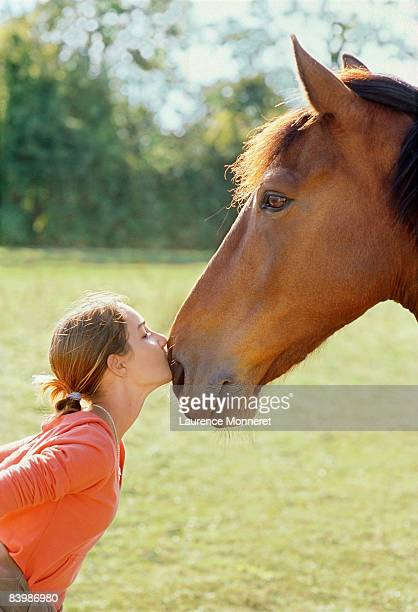 Profile of young girl kissing a horse on nostrils