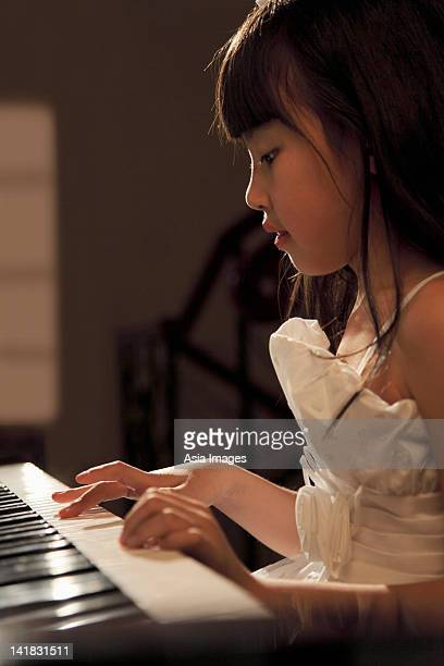 Profile of young girl playing piano