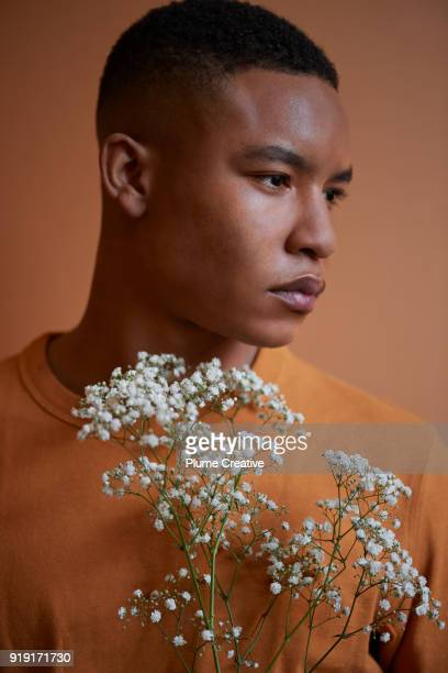 Profile of young man holding flowers
