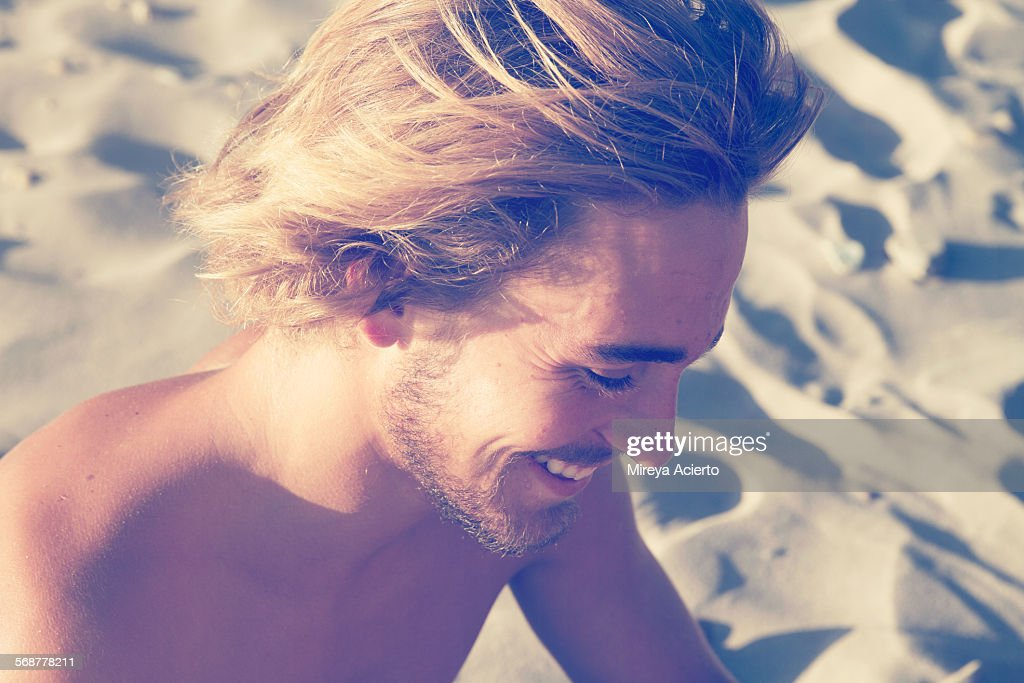 Profile of young man on beach : Stock Photo