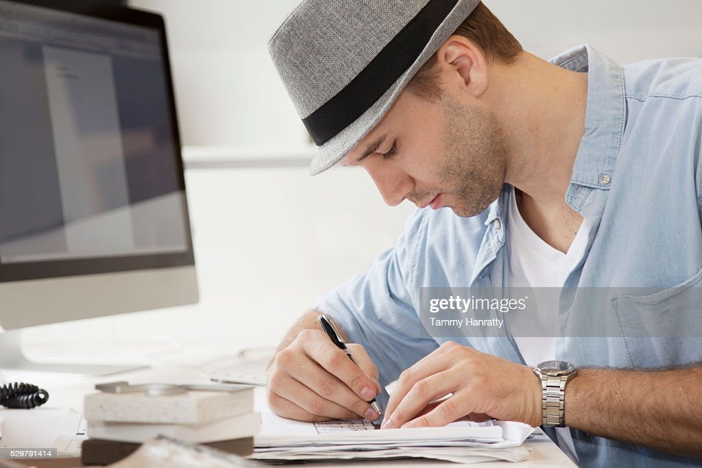 Profile of young man writing at desk : Stockfoto