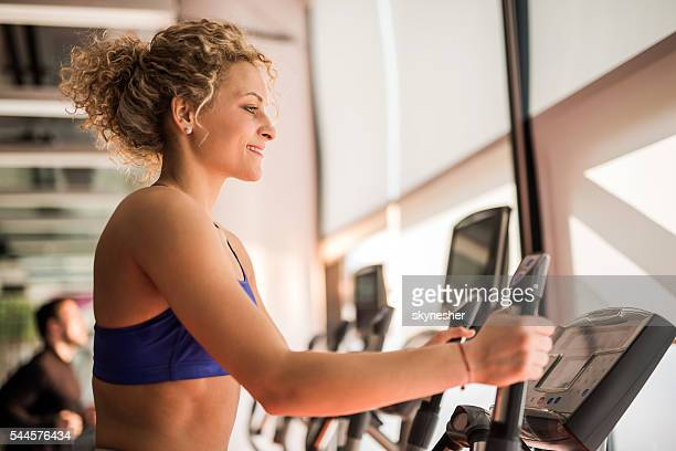 Profile of young smiling woman exercising in health club.