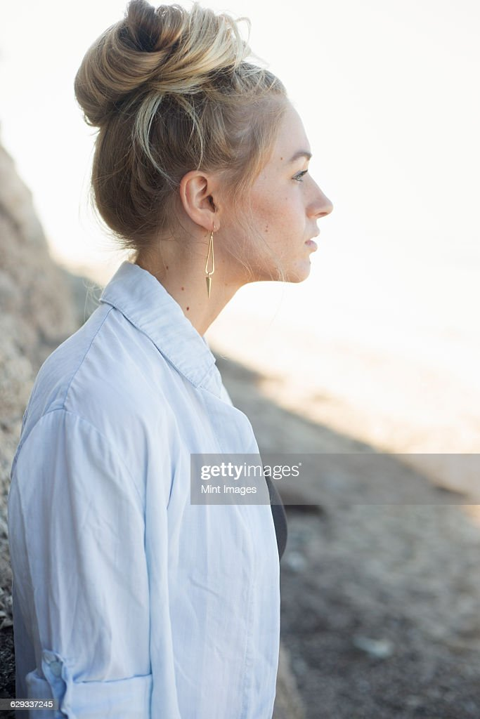 Profile portrait of a blond woman with a hair bun. : Stock Photo