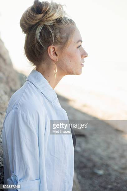 profile portrait of a blond woman with a hair bun. - haar naar achteren stockfoto's en -beelden