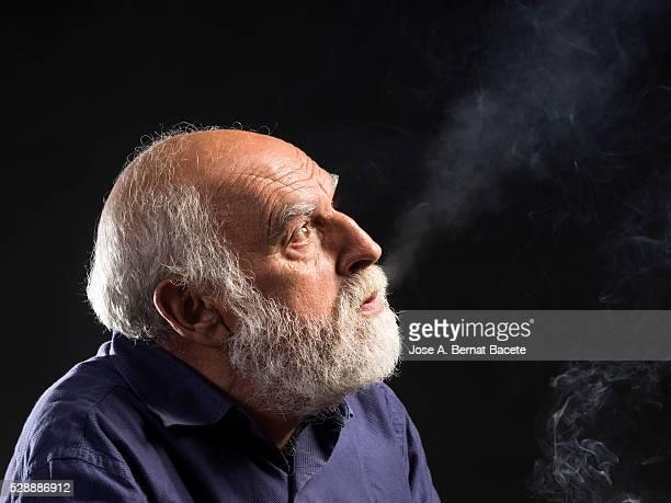 Profile portrait of a smoking man of white beard expelling the smoke