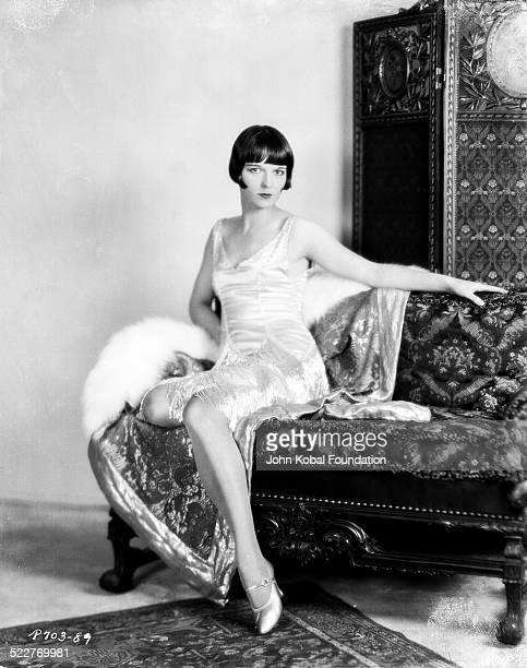 Profile portrait of actress Louise Brooks reclining on a couch in a satin dress for Paramount Pictures 1928