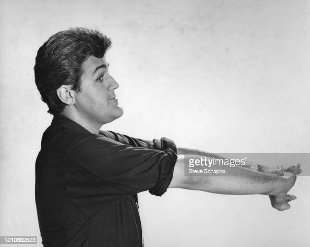 Profile portrait of American comedian and television host Jay Leno as he poses, his arms outstretched, against a white background, Los Angeles,...