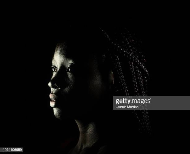 profile portrait of an african woman in shadow - dark stock pictures, royalty-free photos & images