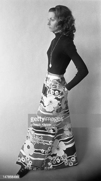 Profile portrait of an unidentified fashion model dressed in a flowered maxi skirt and black turtleneck sweater as she stands against a plain...