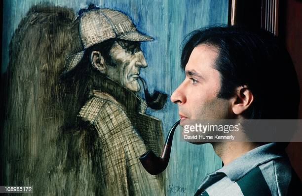 Profile portrait of author screenwriter and director Nicholas Meyer with pipe standing in front of an illustration of Sherlock Holmes that was used...