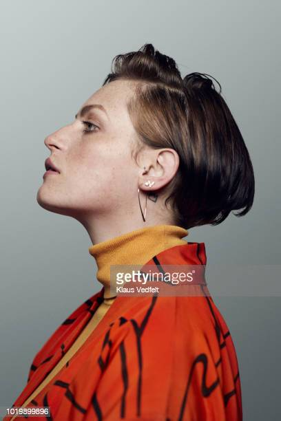 profile portrait of beautiful young woman looking in camera, shot on studio - non binary gender stock pictures, royalty-free photos & images