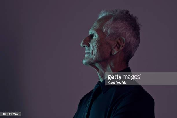 profile portrait of cool mature man, with coloured lights - van de zijkant stockfoto's en -beelden