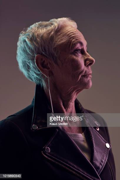 profile portrait of cool mature woman, with coloured lights - van de zijkant stockfoto's en -beelden