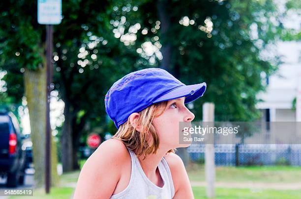 Profile portrait of girl in park wearing baseball cap