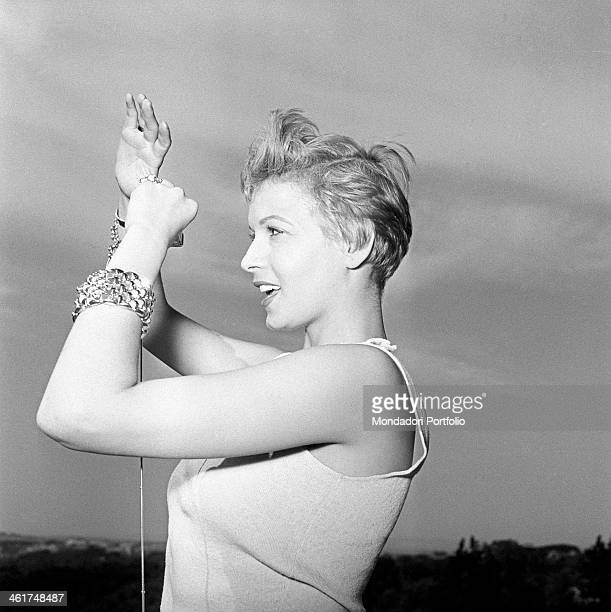 Profile portrait of Isa Barzizza outdoorin the twilight the actress who smiles radiantly with her arms raised wears two glittering gold bracelets...