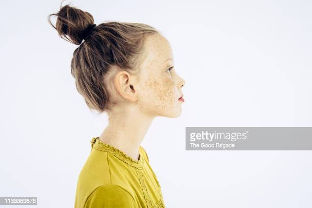 profile portrait of serious young girl looking away - seitenansicht stock-fotos und bilder