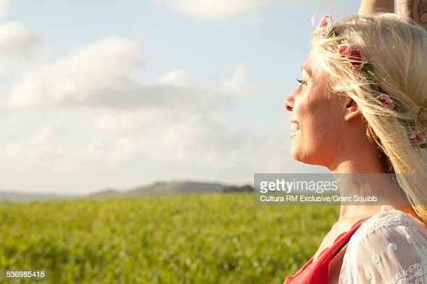 Profile portrait of young woman in rural field