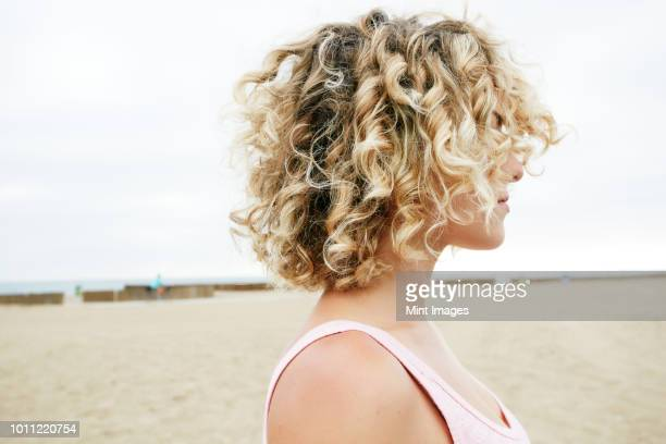 profile portrait of young woman with blond curly hair standing on sandy beach. - curly stock pictures, royalty-free photos & images