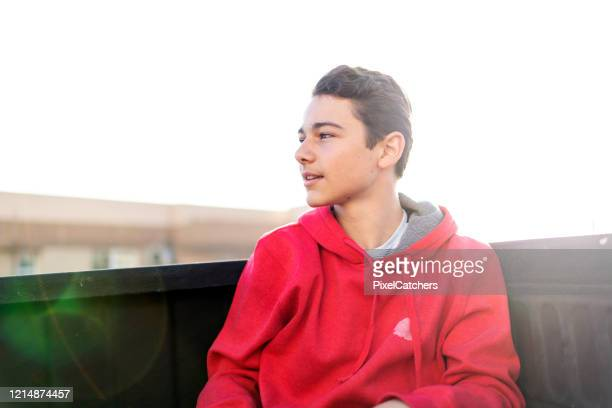 profile portrait teenager sits in back of moving pick-up truck - one teenage boy only stock pictures, royalty-free photos & images