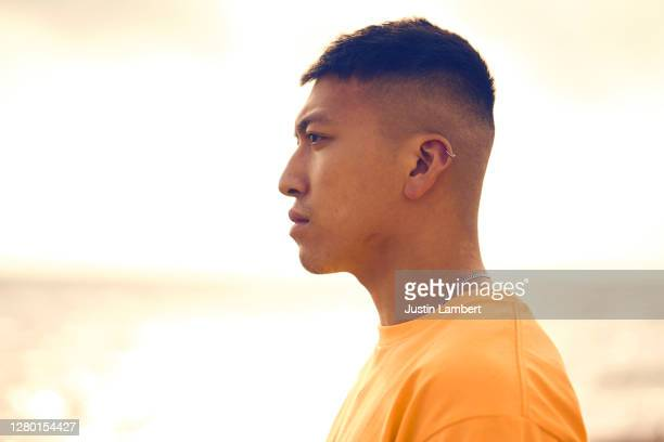 profile shot of a young man standing on a beach in a yellow t shirt - human head stock pictures, royalty-free photos & images