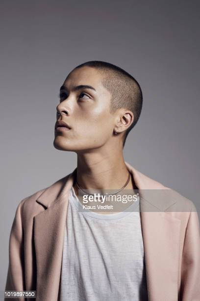 profile shot of beautiful young man looking up, shot on studio - non binary gender stock pictures, royalty-free photos & images