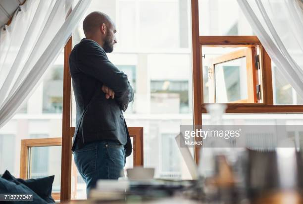 Profile shot of mid adult businessman looking through office window