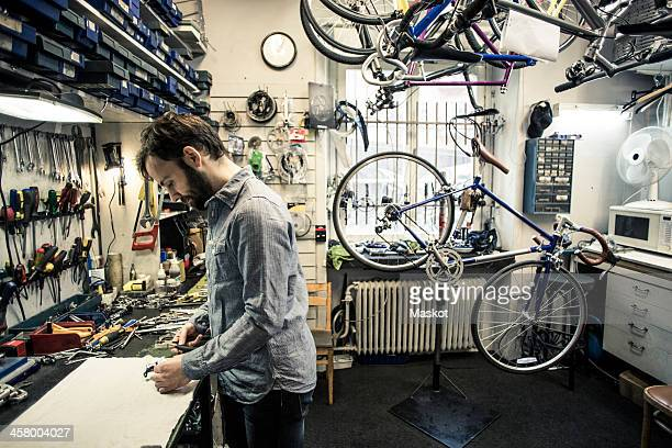 Profile shot of mid adult repairman working at bicycle repair shop