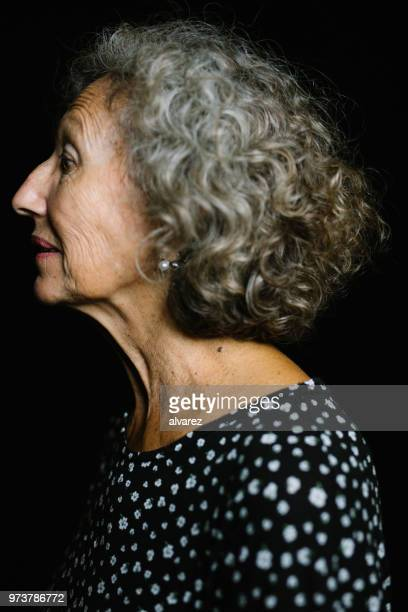 Profil-Shot Of Senior Woman auf schwarzem Hintergrund