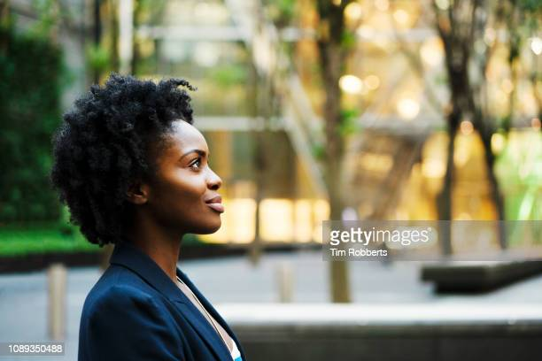 profile shot of woman looking ahead - afro frisur stock-fotos und bilder