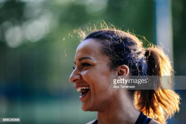 profile shot of young woman smiling in outdoor sports court