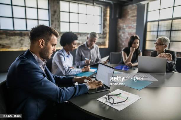 vista de perfil de um homem de negócios usando o laptop em uma reunião no escritório. - reunião de negócios - fotografias e filmes do acervo