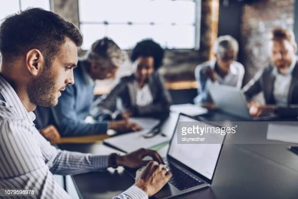 vista de perfil de um homem de negócios usando o laptop em uma reunião no escritório. - grupo médio de pessoas - fotografias e filmes do acervo