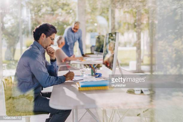 Profile view of a businessman writing a plan in the office.