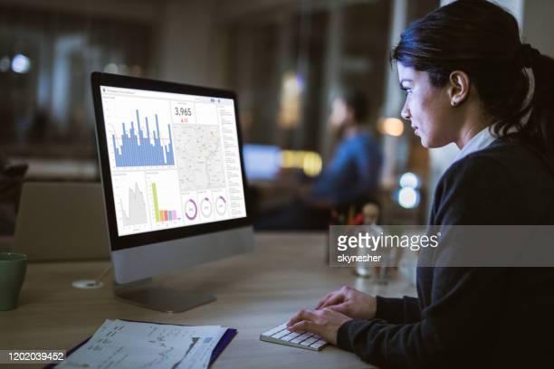 visão de perfil de uma empresária analisando gráficos em um computador no escritório. - examinar - fotografias e filmes do acervo